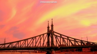 A stunning pink dusk backlights the ornate Freedom Bridge